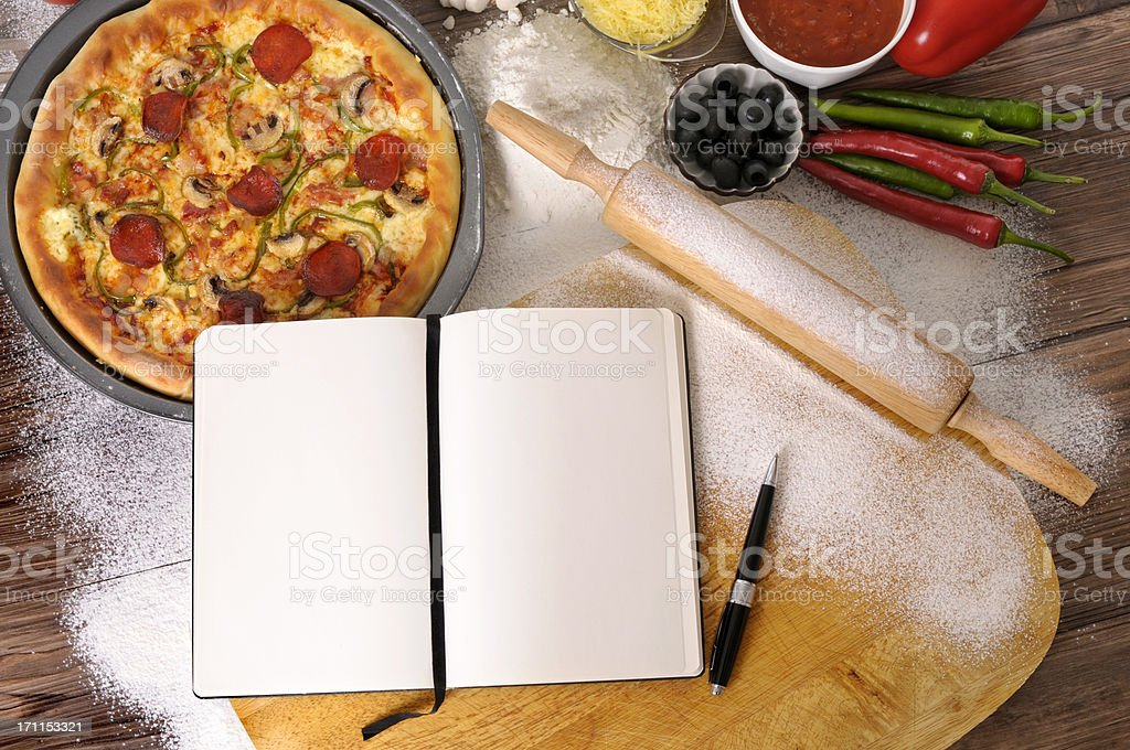 Pizza with notebook and ingredients royalty-free stock photo