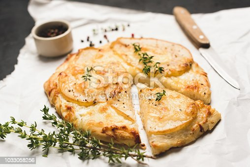 Pizza with pear, cheese and thyme on parchment paper. Mini pizza with pear slice cut out
