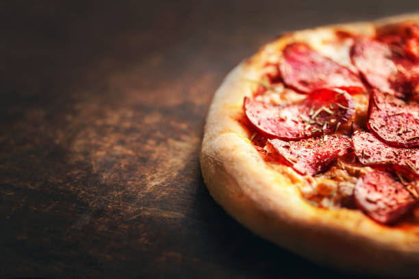 Pizza with pepperoni and salami on a rustic wooden table. stock photo