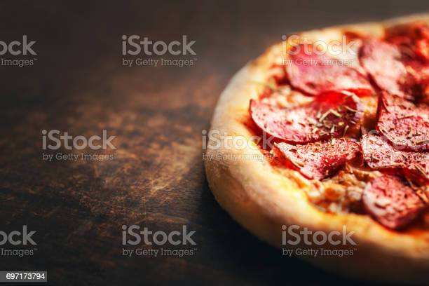 Pizza with pepperoni and salami on a rustic wooden table.