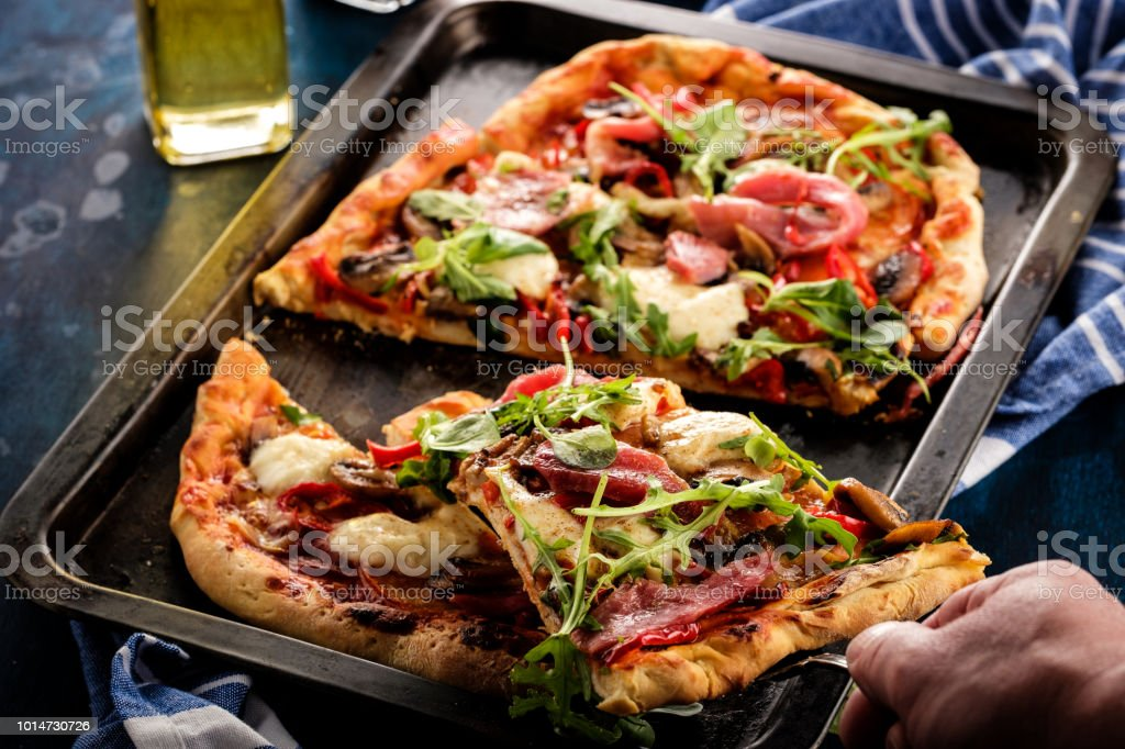 Pizza with prosciutto, mozzarella, mushroom and rocket salad with spices on blue background. A human hand takes a piece of pizza стоковое фото