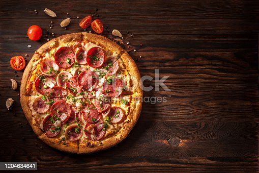 Pizza with salami, ham, bacon, garlic and fresh herbs. Rustic style. Top view. Copy space.