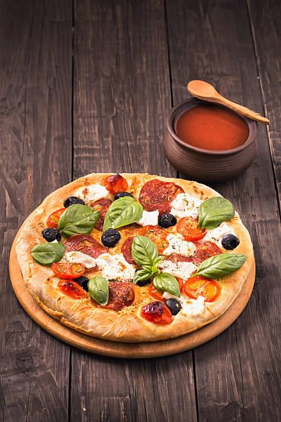 Cтоковое фото Пицца с салями, моцареллой и базиликом