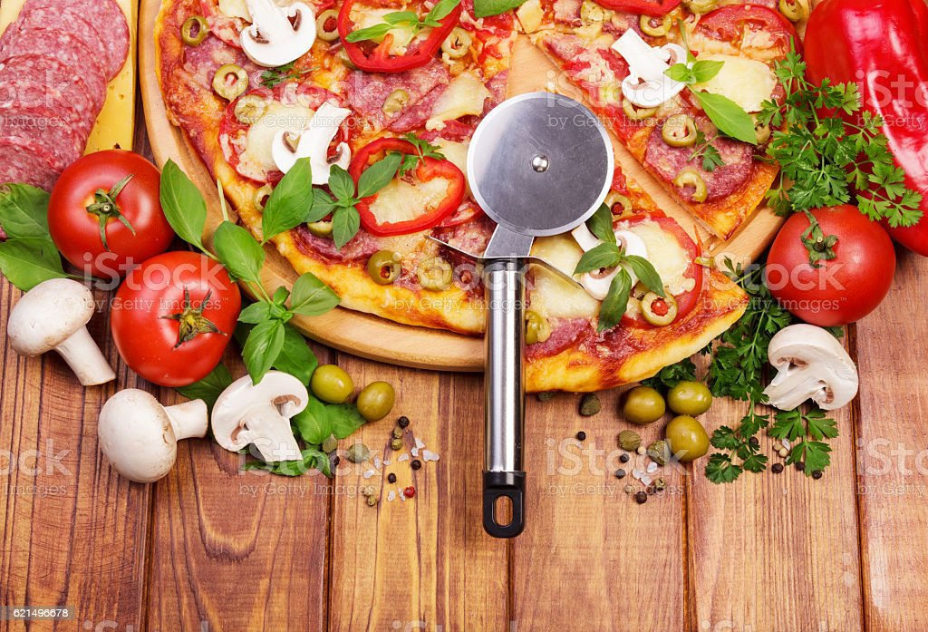 Pizza with salami, mushrooms, peppers, cheese, knife on dark wood. Lizenzfreies stock-foto