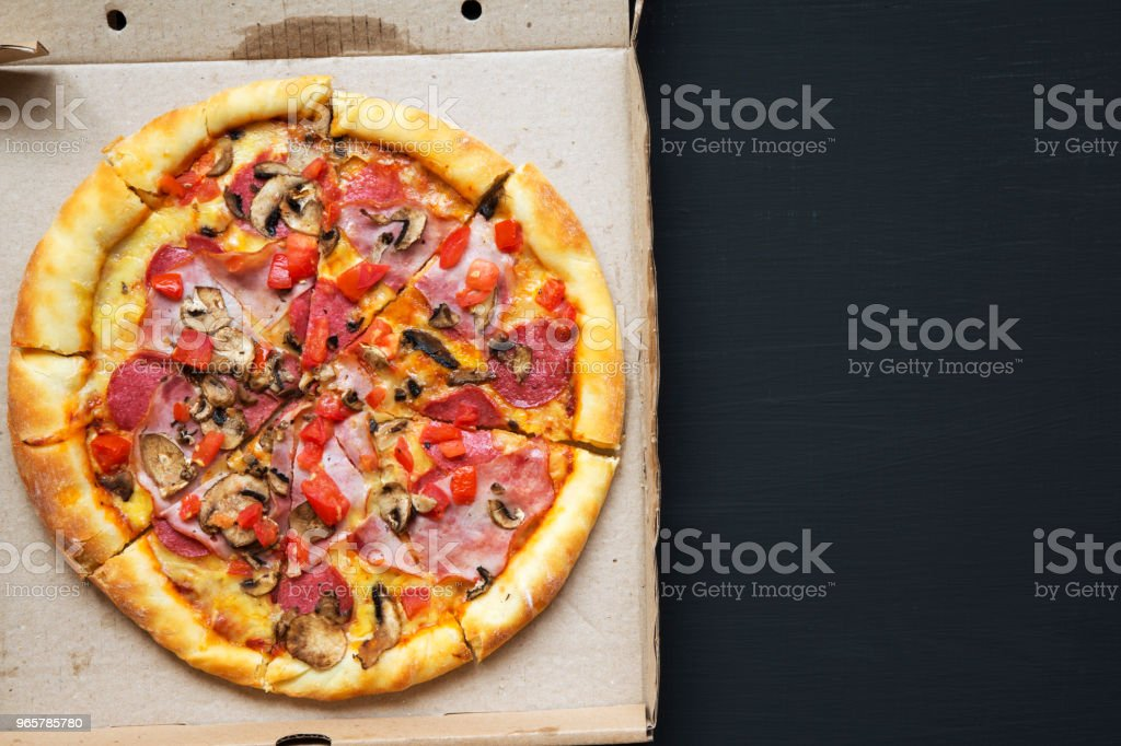 Pizza with tomatoes, bacon, salami, cheese and mushrooms in a cardboard box on dark background, top view. Copy space. From above, flat lay. Pizza with tomatoes, bacon, salami, cheese and mushrooms in a cardboard box on dark background, top view. Copy space. From above, flat lay. Above Stock Photo