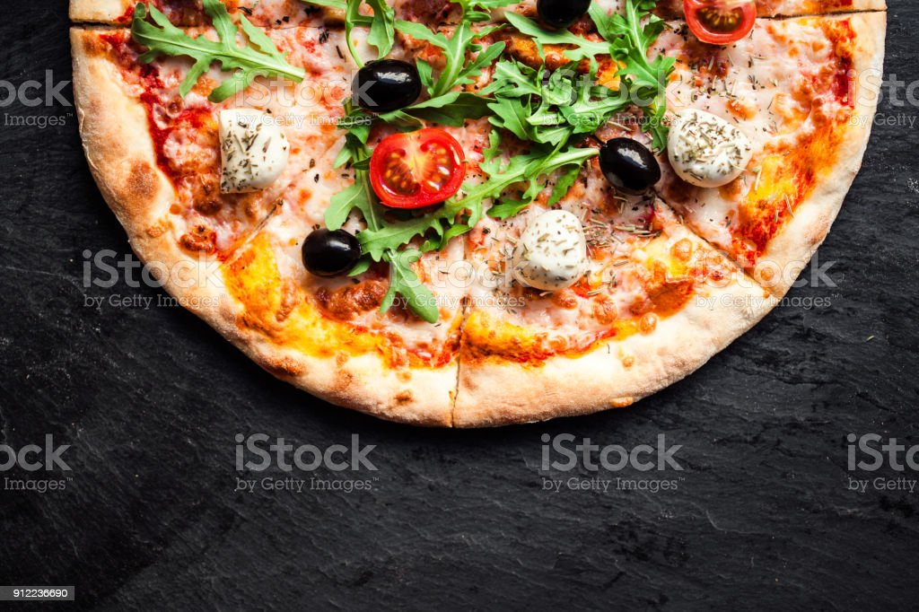 Pizza with tomatoes, mozzarella cheese and arugula. Pizza menu.Top view with copy space on dark stone table stock photo