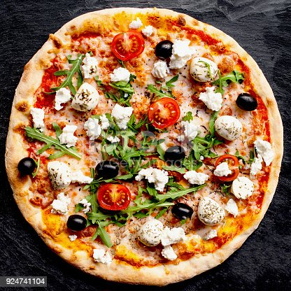 istock Pizza with tomatoes, mozzarella cheese and arugula. Pizza menu.Top view with copy space on dark stone table 924741104