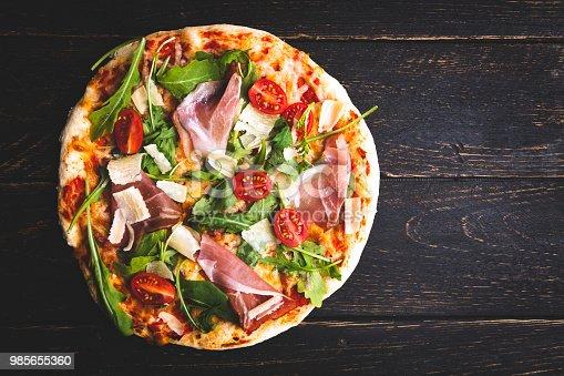 istock Pizza with tomatoes, mozzarella cheese ham and arugula. 985655360