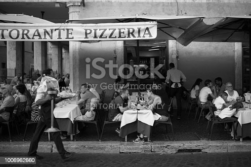 Rome, Italy - July 12, 2015. A quaint pizzeria on a side street in Rome, Italy. People sitting outside eating pizza while shop owner stands in the doorway. Other people walking by on street.