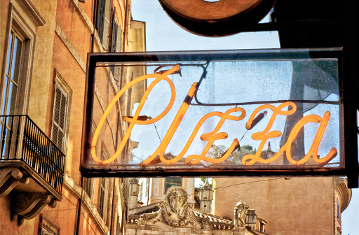 Pizzeria sign on ancient buildings