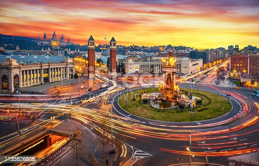 Long exposure photo of Fira de Barcelona, Plaça d'espanya (Spain square) and montjuic mountain in Barcelona at sunset with car light trails . Spain