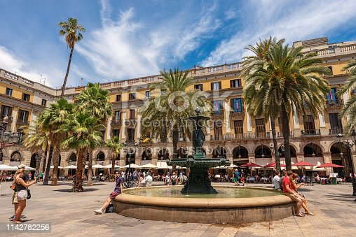 Barcelona, Spain - June 13, 2014: Placa Reial or Plaza Real (Royal square), with the bronze fountain of the Three Graces, in the Barri Gotic quarter of Barcelona, Catalonia, Spain. It lies next to La Rambla. Some tourists and locals relax sitting on the fountain or in the numerous bars and restaurants in the shade of umbrellas