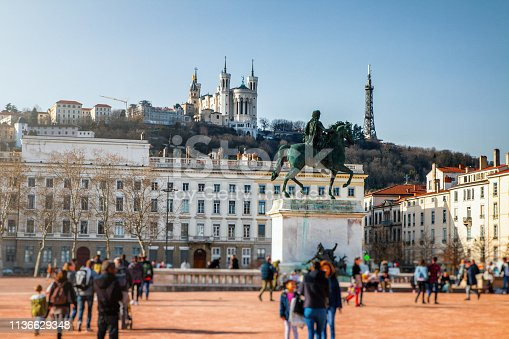 Place Bellecour in Lyon french city in sunny early spring season day, with some tourist people and with equestrian statue of Louis XIV in middle of this big famous town square. This photo was taken in Lyon city, in Rhone department in Auvergne-Rhone-Alpes region, in France (Europe) in february. We can also see the hill of Fourviere with the Basilica Notre Dame de Fourviere and the famous telecommunication antenna tower.