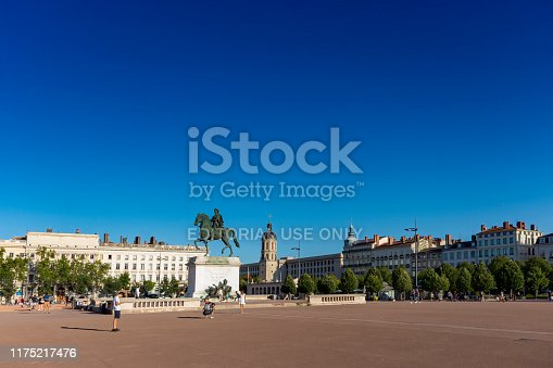 Overview of the Place Bellecour, It is one of the largest open squares in Europe. In the middle is an equestrian statue of King Louis XIV by François-Frédéric Lemot. Tourists are walking across the square. A typical summer day in Lyon, France
