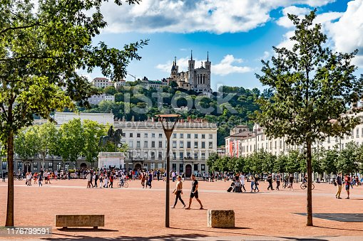 Overview of the Place Bellecour, It is one of the largest open squares in Europe. In the middle is an equestrian statue of King Louis XIV by François-Frédéric Lemot. Tourists are walking across the square in the foreground with the Basilica Notre Dame on the hill in the background. A typical summer day in Lyon, France