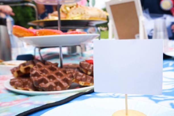legen sie karte für einen gast bei einem tee-party-picknick für eine brautdusche. raum für kopie auf dem stehenden namensschild, als tischdekoration. - brautparty kuchen stock-fotos und bilder
