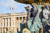 Place de la Concorde fountain statues with golden details and building with french flag in a sunny day in Paris