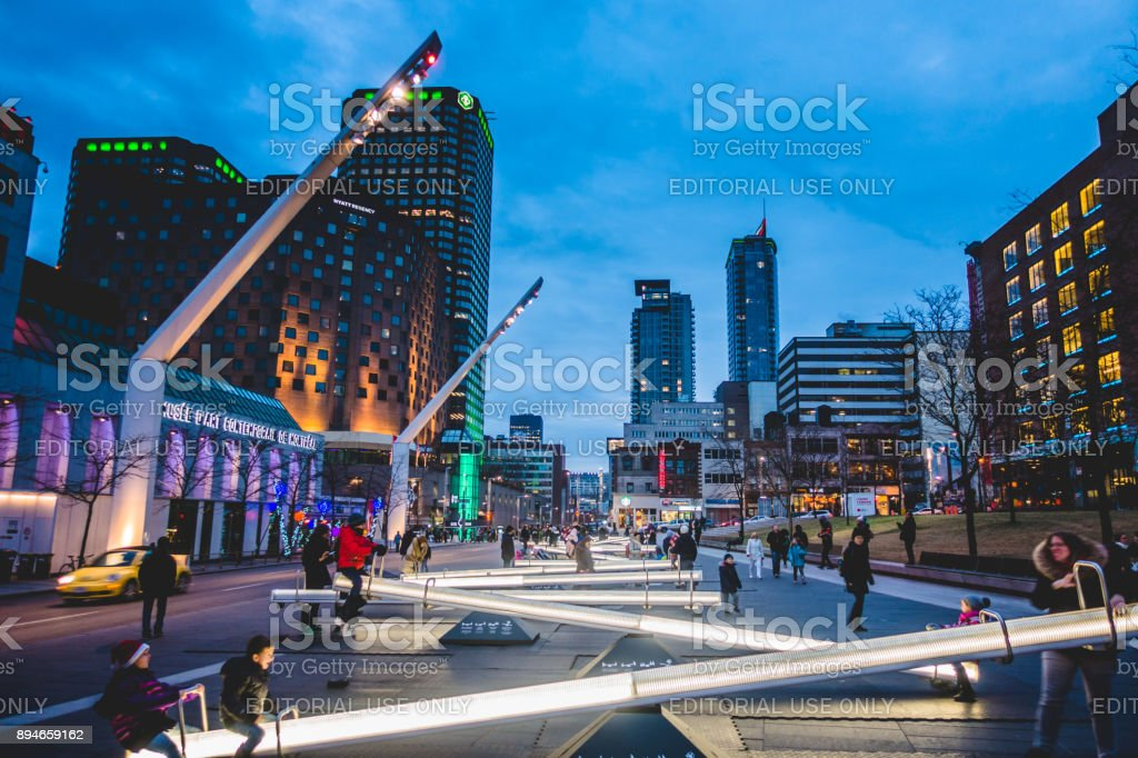 Place Des Arts Square are Night with Kids and Parents having Fun on Seesaws that Change Light Intensity and also Makes Music. stock photo