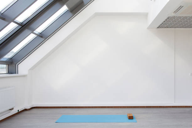 A place for sports training in yoga and fitness A place for sports training. Mat and supporting unit for yoga and fitness lying on the floor. The room is flooded with daylight sunlight from the window, the glare on the wall. yoga studio stock pictures, royalty-free photos & images