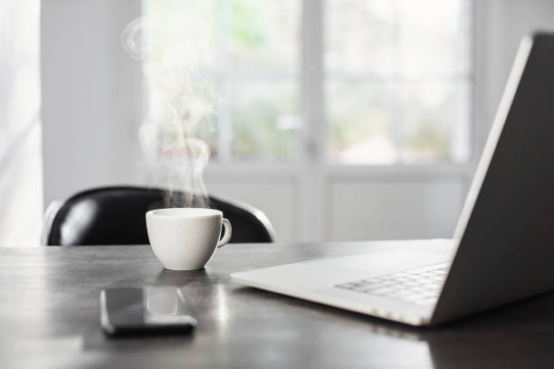 Place of work. Laptop, smartphone and hot coffee at desk stock photo