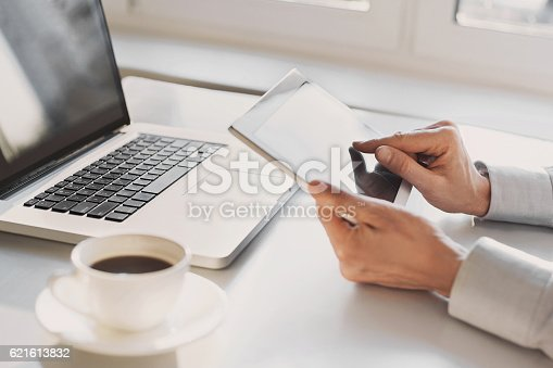 879813798istockphoto Place of work, man using tablet and laptop 621613832