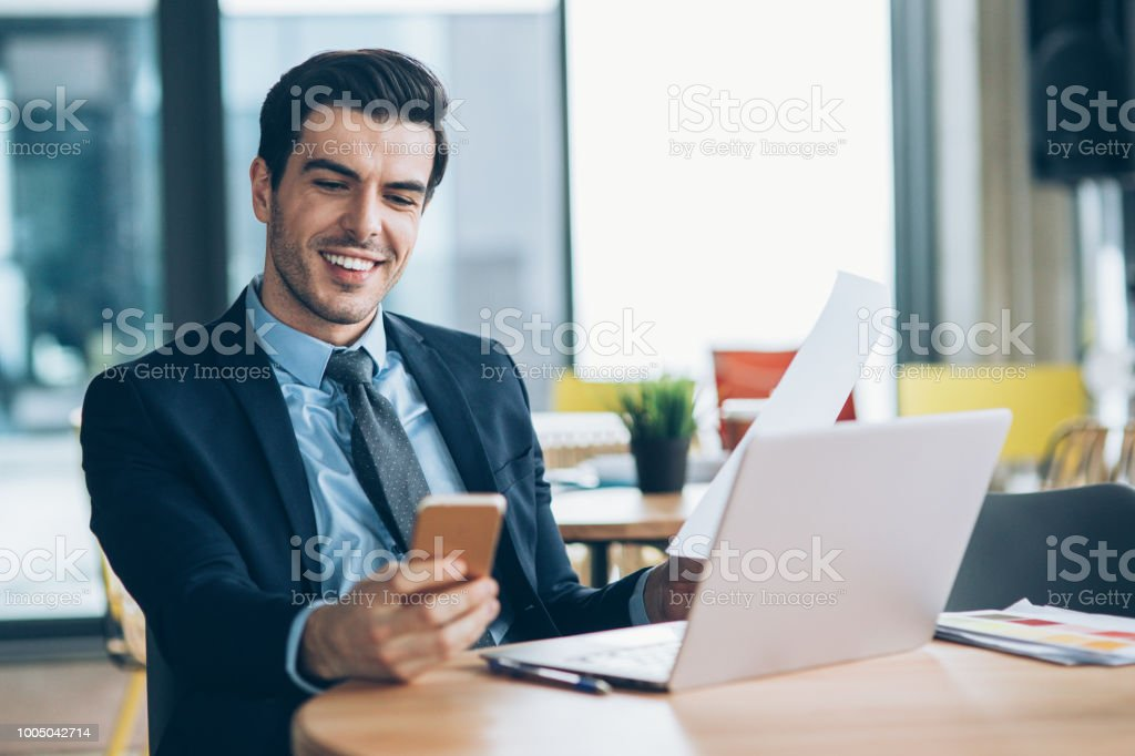 Businessman using laptop, smart phone and documents in cafe