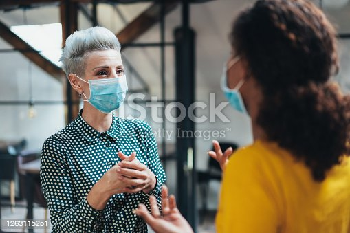 Colleagues businesswomen in the office talking while wearing medical face mask