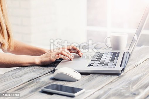 Close-up of female hands on laptop keyboard