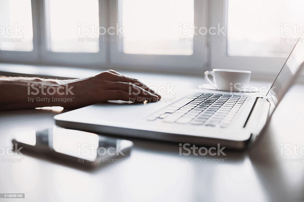 Close-up of male hand on laptop keyboard