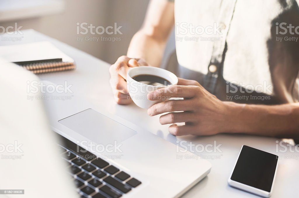 Male hands holding cup of coffee in the office