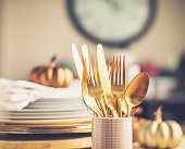 Place setting for Thanksgiving dinner with beautiful gold cutlery