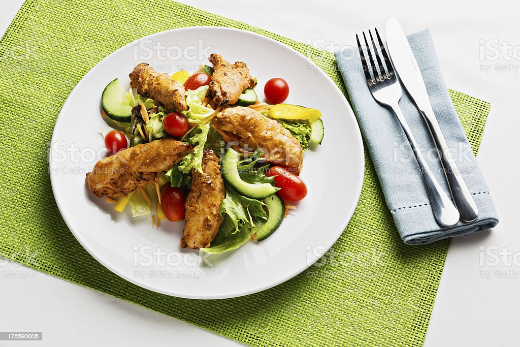 Place setting of luscious low-carb spiced chicken and salad royalty-free stock photo