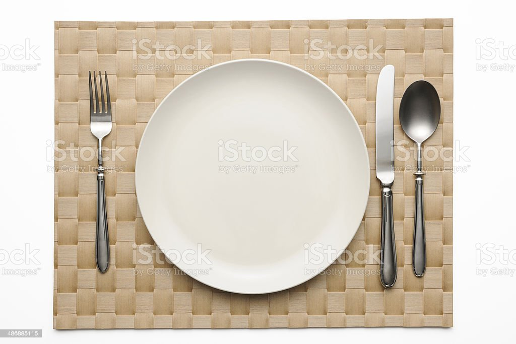 Place setting on brown place mat on white background stock photo