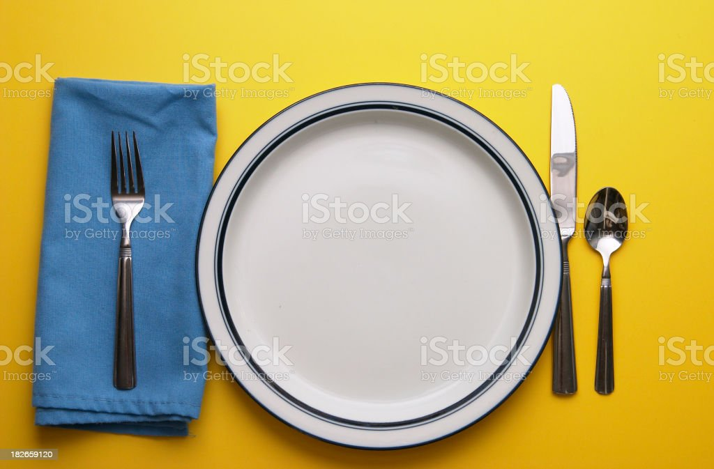 Place Setting on Yellow with Empty Plate royalty-free stock photo