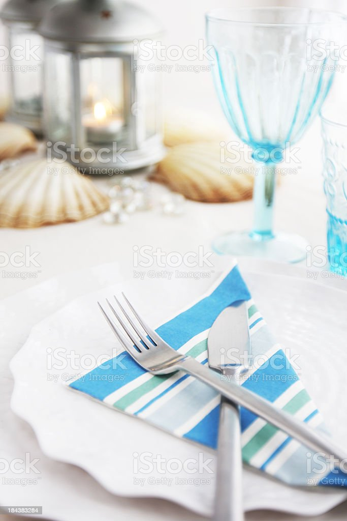 Place setting with blue striped napkin on scalloped dishes royalty-free stock photo