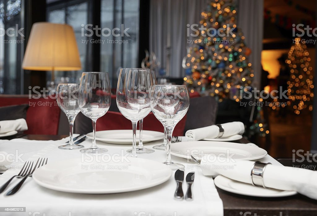 Place setting with Christmas tree in background stock photo