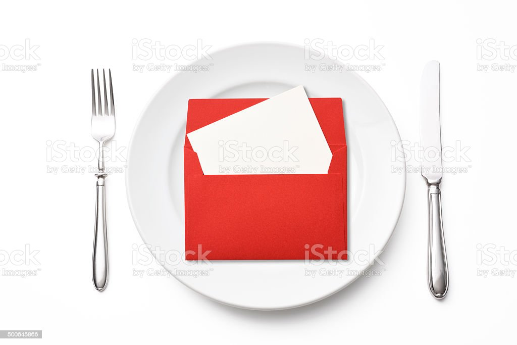 Place setting with red envelope on white background stock photo