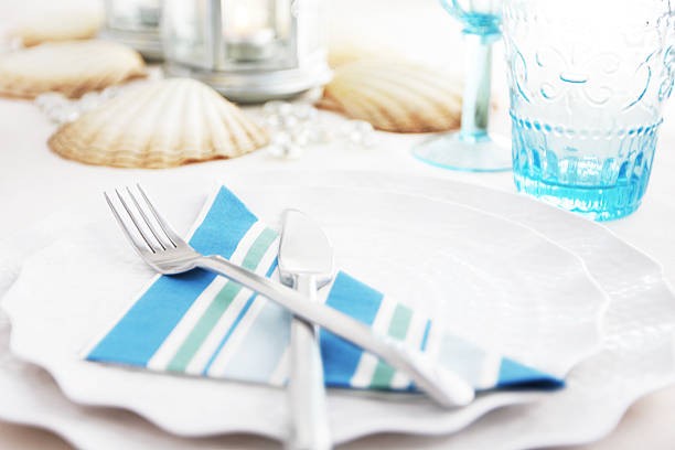 place setting with shells blue striped napkin on scalloped dishes - blue table setting stock photos and pictures