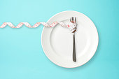 istock Place setting with steel fork and measuring tape on blue background 929866442