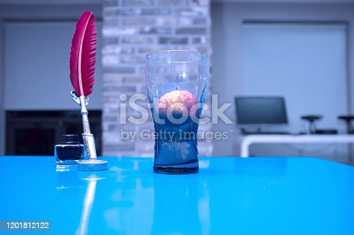 Blue table, glass cup, quill pen, ink, fruit, office background,