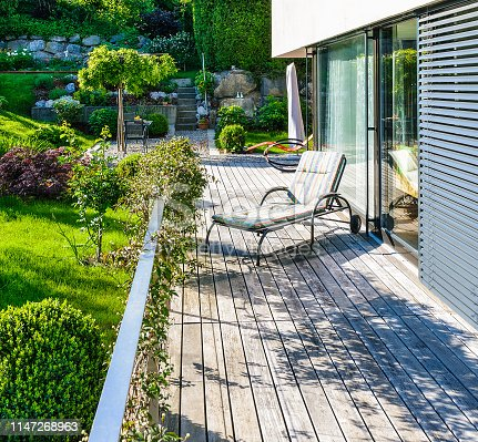 Green garden of a comfortable, modern family house. The large wooden terrace and the deck chairs invite to relax and sunbathe after a busy day.