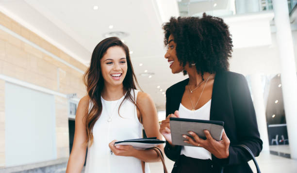 Places to go, careers to build Shot of two young businesswomen having a conversation while walking through a modern office women goals stock pictures, royalty-free photos & images