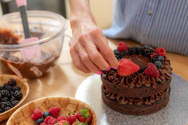 Placing a large strawberry on a vegan chocolate cake stock photo