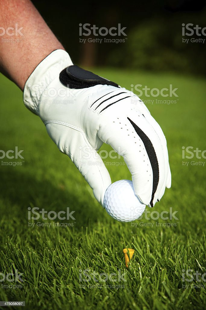 placing golf ball on tee royalty-free stock photo