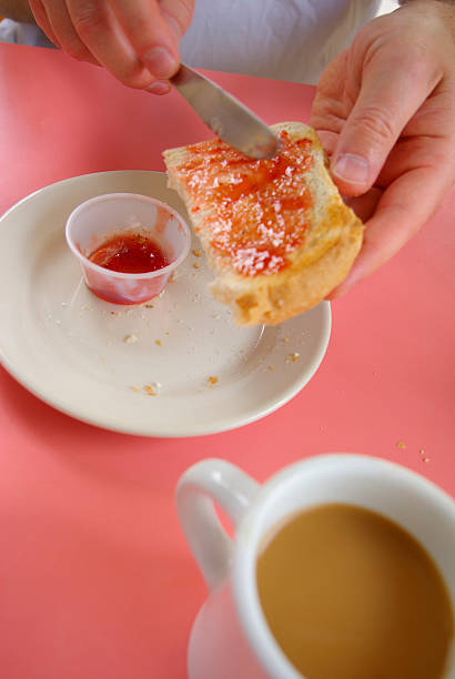 placing jam on bread with coffee - mikefahl stock pictures, royalty-free photos & images