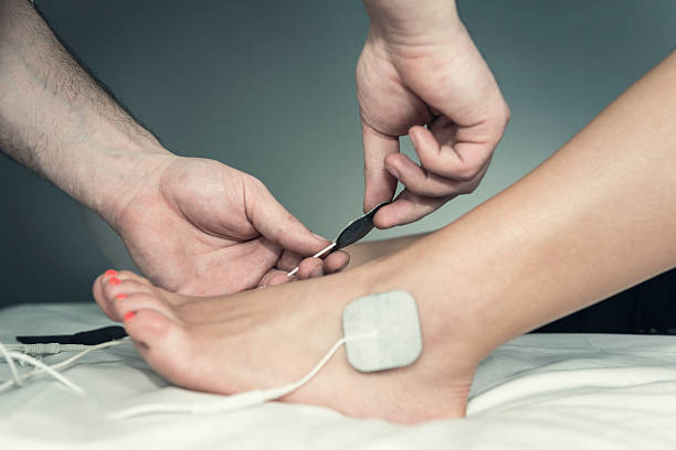 Placing TENS electrodes on foot stock photo
