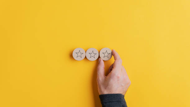 Placing three wooden cut circles with star shape on them in a row stock photo