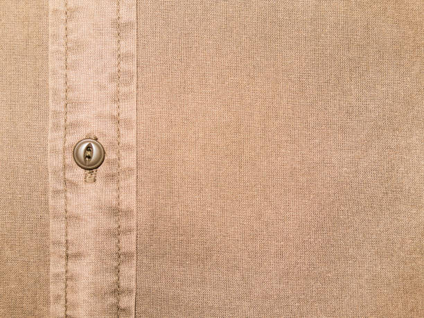 textura de camisa de algodão bege liso com botão em close-up - foto de acervo