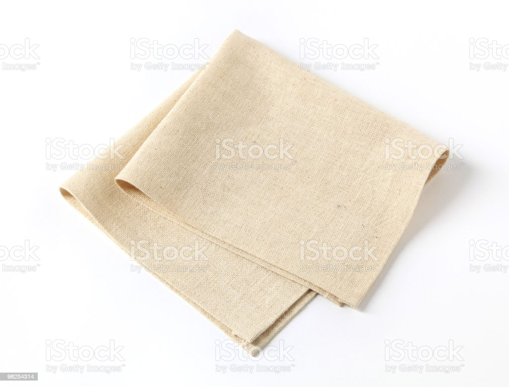 A plain beige fabric napkin folded in half royalty-free stock photo