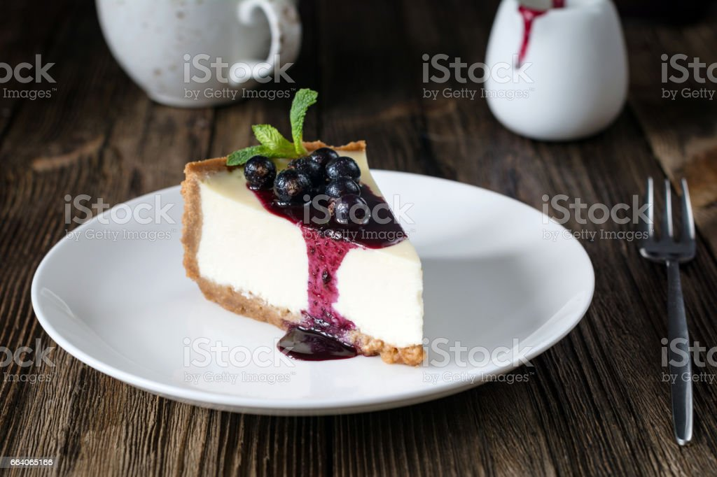 Plain cheesecake with black currant sauce stock photo